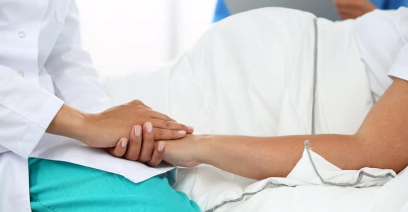 Friendly Female Medicine Doctor's Hands Holding Pregnant Woman's