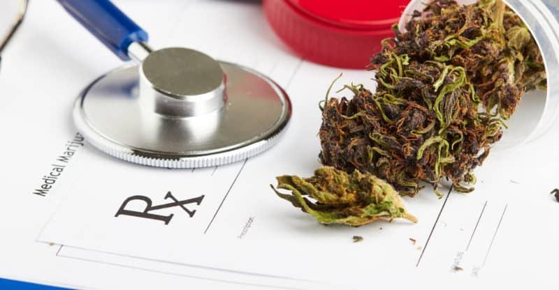 Medical marijuana in jar lying on prescription form near stethoscope.
