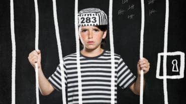 Closeup of sad bad boy wearing jail suit and kept behind bars. Portrait of little prank in jail. Sad male kid wearing striped clothes.