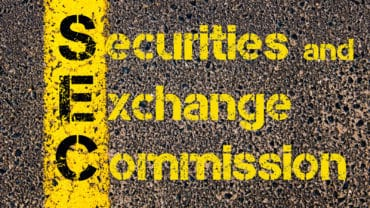 Acronym SEC Securities and Exchange Commission written over road marking yellow paint line.