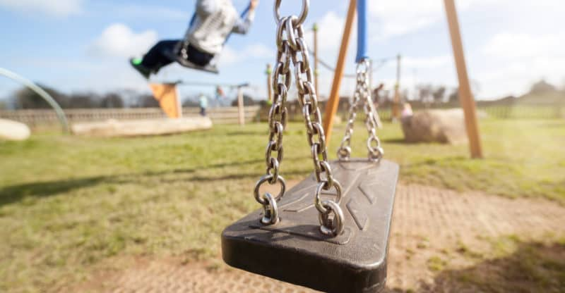 Empty playground swing with children playing in the background c