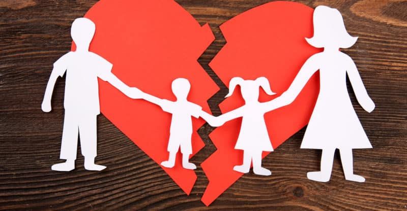 Paper cutout silhouette of a family split apart on a paper heart
