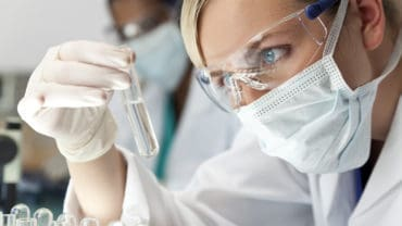 Female Scientific Research Team With Clear Solution In Laborator