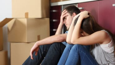 Angry evicted couple worried moving house sitting on the floor in the kitchen