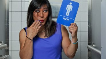 Transgender female in restroom stall with men's restroom sign in hand, surprised with fingers over mouth.