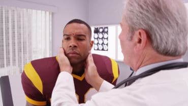 College football player having senior doctor review his concussion injury.
