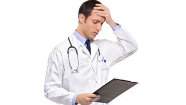 A doctor banging his head realizing a mistake he forgot isolated on white background