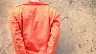 Handcuffed Prisoners with orange clothes waiting for Death Penalty
