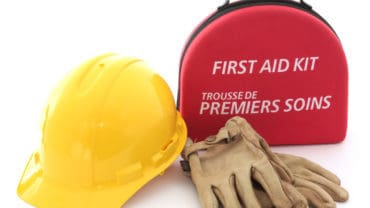 A first-aid kit hardhat and gloves spell out the need for safety in the workplace.
