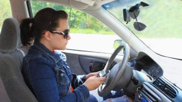 Teen drives car while distracted by text messaging on cell phone