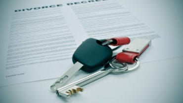 a divorce decree document and the keys of a car and a house