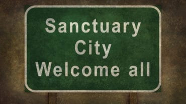Sanctuary city welcome road sign illustration with distressed foreboding background