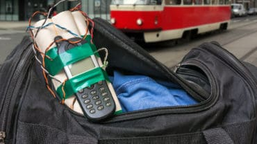 Dynamite bomb with phone in terrorist bag on street of city - terrorism concept