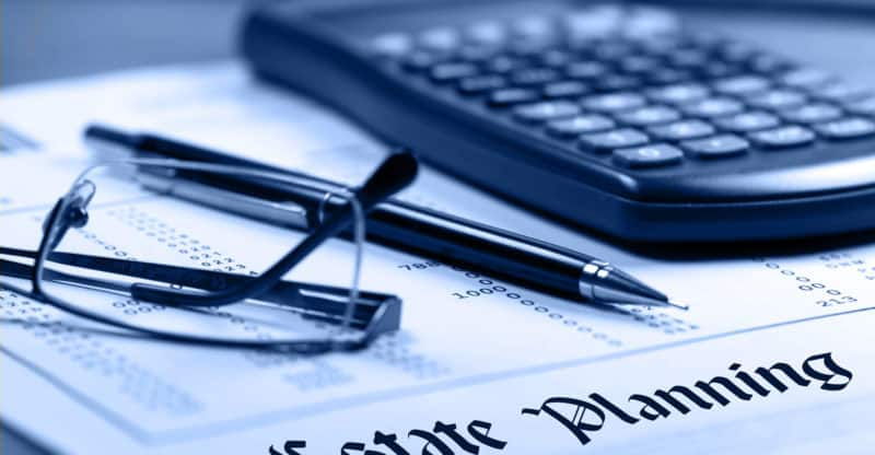 Estate planning. Calculator, glasses and black pen on financial documents