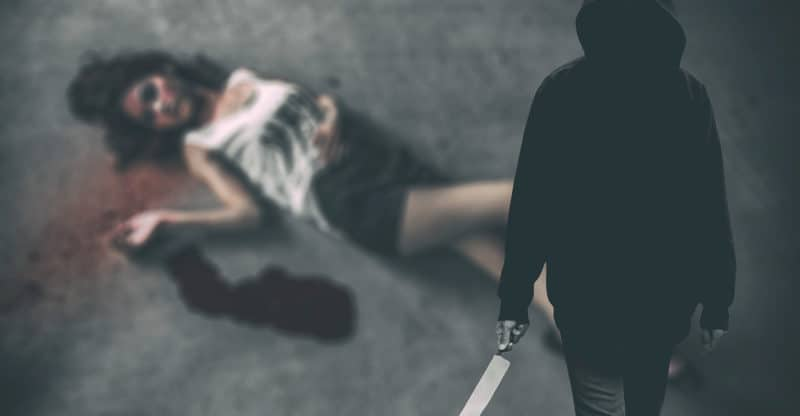Murderer hooded man ready to attack to kill his victim that is the woman to died on ground. (Criminal concept)