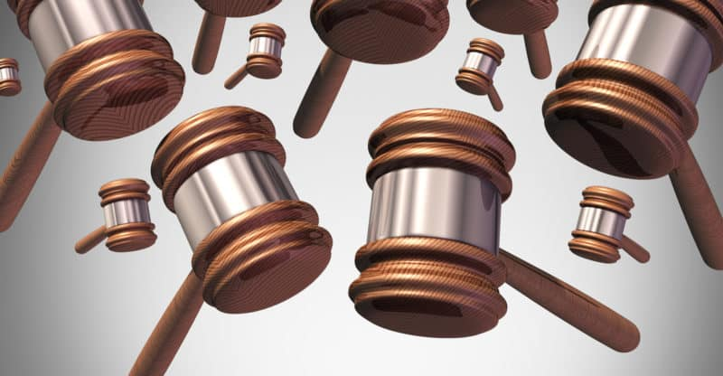 Class action lawsuit concept as a plaintiff group represented by many judge mallets or gavel icons coming down as a symbol for social litigation or organized legal legislation.