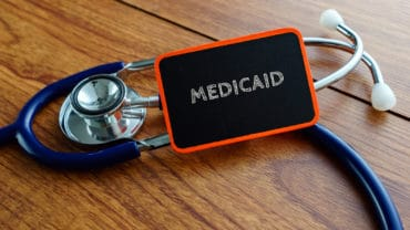 Medical concept.Word MEDICAID with stethoscope on wooden table.