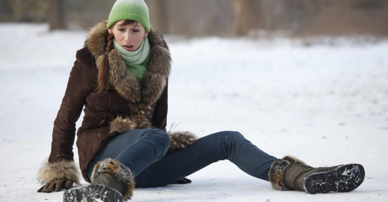 woman slips and falls down on snowy road