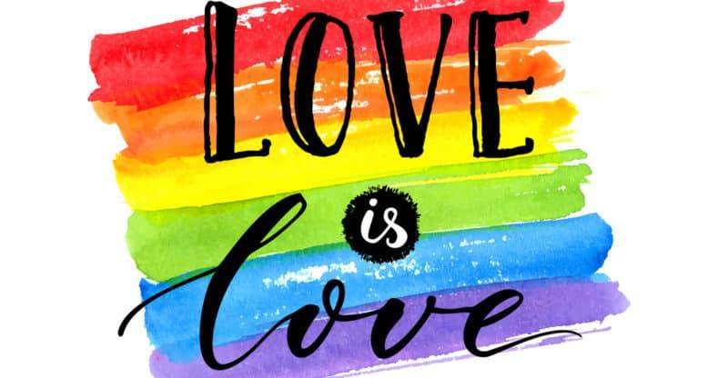 Love is love - LGBT pride slogan against homosexual discrimination. Modern calligraphy on rainbow watercolor flag