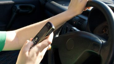 Woman driving while making a text message