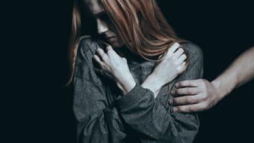 Fearful rape victim man holding her arm black background