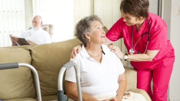 Senior woman in a nursing home with a caring nurse.