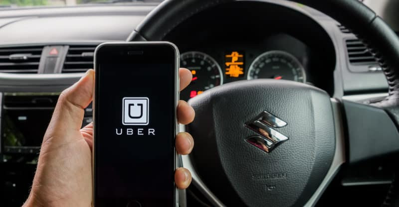 CHIANG MAITHAILAND - JULY 292016 : A MAN hand holding Uber app showing on iphone 6s. Uber is smartphone app-based transportation network in suzuki swift eco car.
