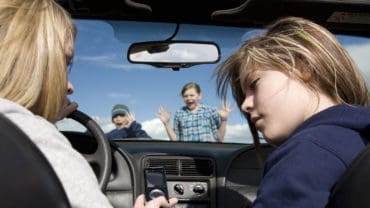 Two teenagers being distracted by a cell phone text instead of watching the road. They are about to hit a boy and girl crossing infront of the car.