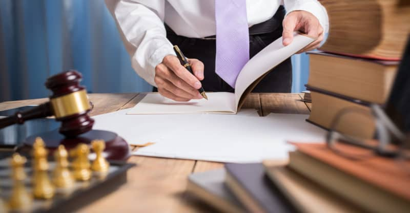 Young lawyer business man working with paperwork on his desk in office workplace consultant lawyer concept hipster view of photography.
