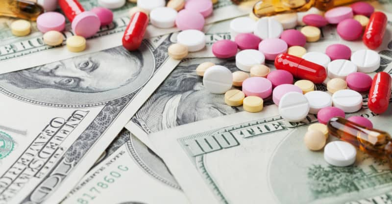Heap of pharmaceutical drug and medicine pills scattered on dollar cash money. Cost of medicinal product and treatment concept.