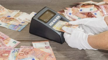 A person uses a automatic counterfeit money detector with white gloves