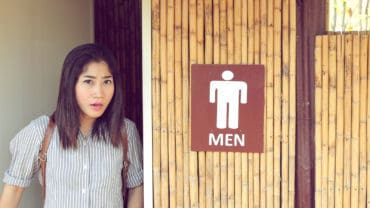 transgender woman leave from the men's toilet looking straight and upset.