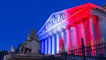 The French National Assembly lit up with colors of French national flag at night, Paris, France.