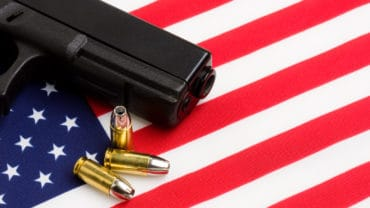 gun over american flag modern 9mm handgun with bullets