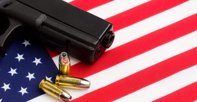 gun over american flag modern 9mm handgun with bullets