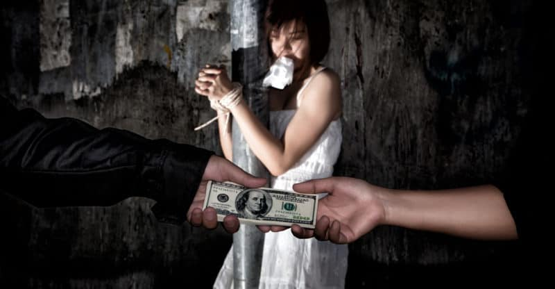 Human trafficking concept. Person hand with a dollar banknote buying victim woman in pain and bound hands with rope. missing kidnapped. in dark tone.