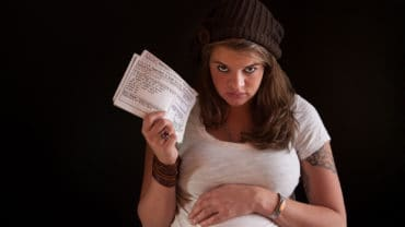 Unhappy pregnant woman with food coupons over black background