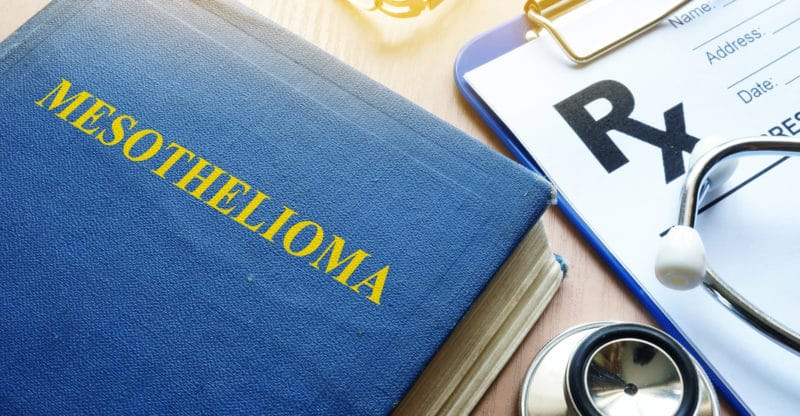 Book about Mesothelioma and stethoscope on a table.