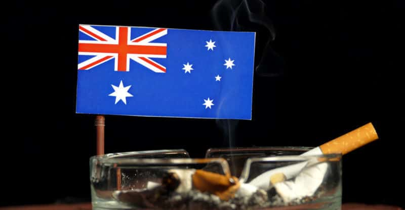 Australian flag with burning cigarette in ashtray isolated on black background