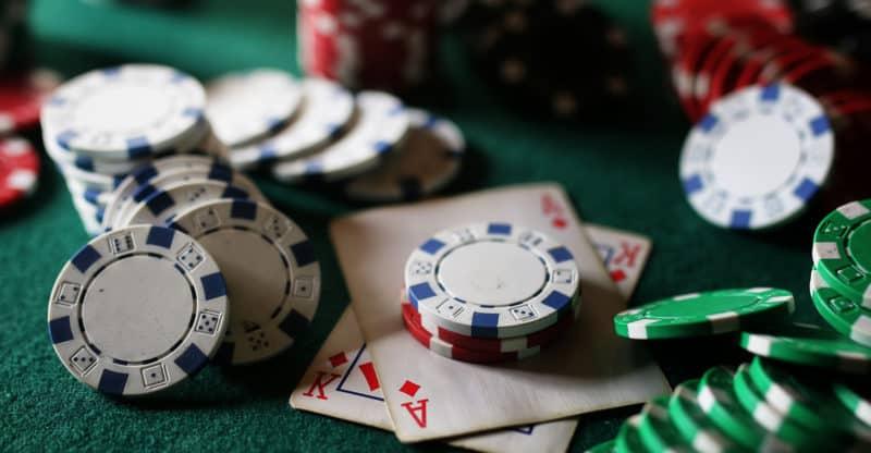 set of gambling chips and cards on green baize gambling casino