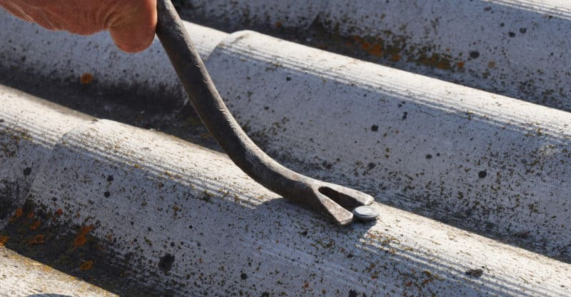 Asbestos workers repair asbestos roof. Asbestos removal. How to pull out the nails correctly from asbestos old roof tiles. Roof worker repair dangerous asbestos old roof tiles. Roofing construction.