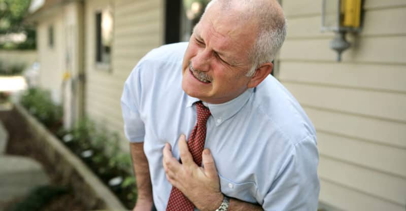 A mature businessman doubled over clutching his chest. He appears to be having a heart attack.