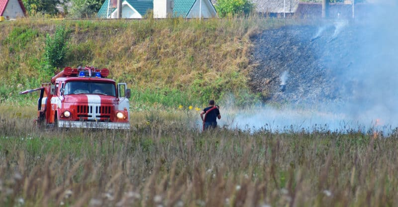 Fire truck and firefighter on firefighting rescue operation fighting with flames in burning meadow near to railway in hot summer day. Firefighting rescue operation concept.